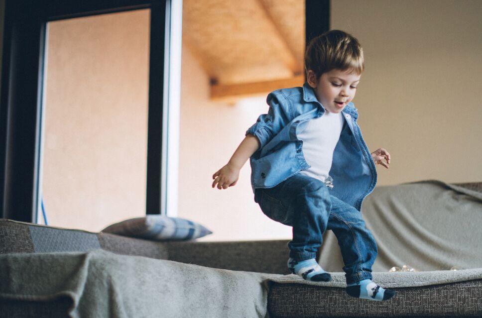 Little boy jumping with joy on sofa