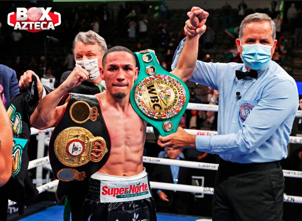 Gallo Estrada posa con sus cinturones Supermosca.