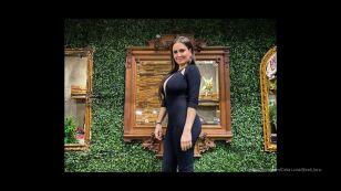 Celia Lora  de perfil con jumpsuit negro entallado con escote profundo.