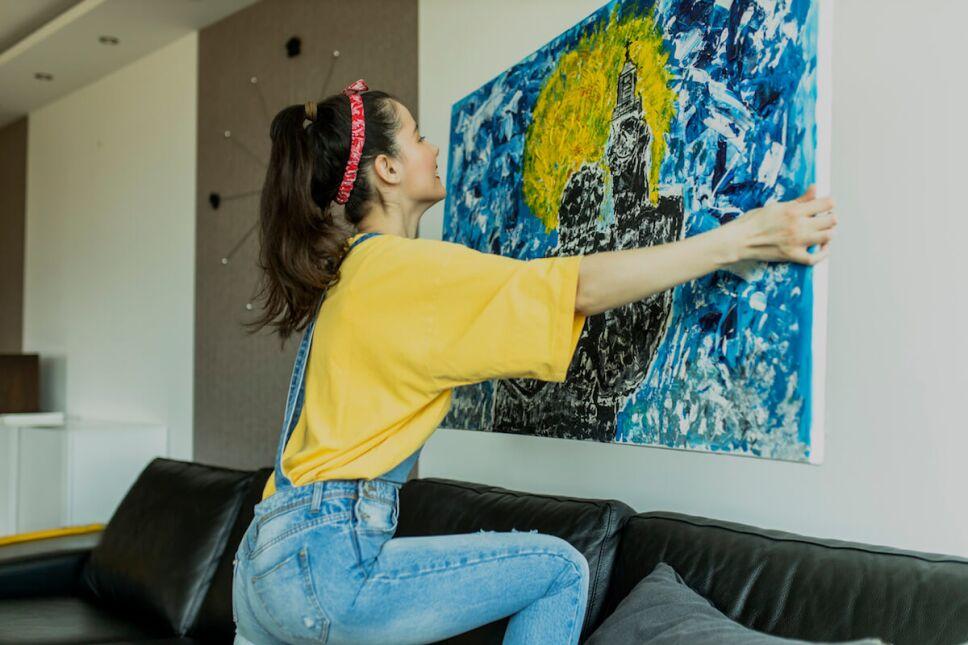 mujer colgando arte en su sala