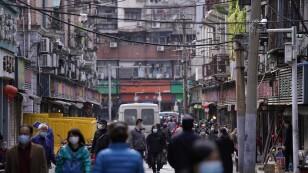 People wearing face masks walk on a street market in Wuhan