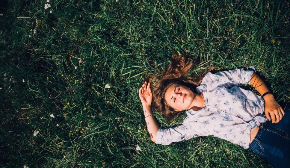 mujer recostada en el pasto con los ojos cerrados