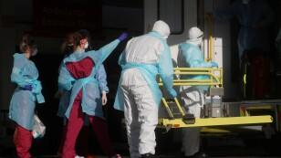Personal médico con ropa de protección saca a un paciente de una ambulancia en el hospital de St Thomas, en Londres