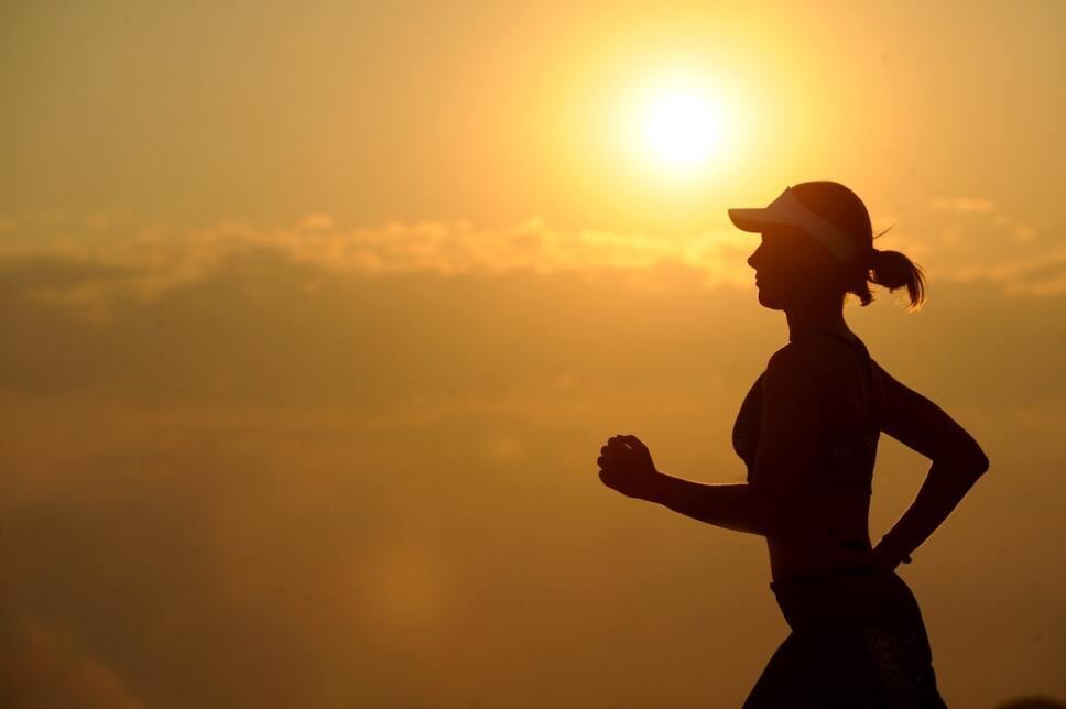 mujer corriendo contra la puesta del sol para bajar de peso y dormir mejor