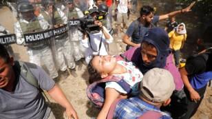 Foto del lunes de migrantes en viaje a EEUU llevando a una niña cerca de la frontera entre Guatemala y México
