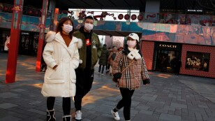 People wearing face masks walk past luxury boutiques in the Sanlitun shopping district in Beijing