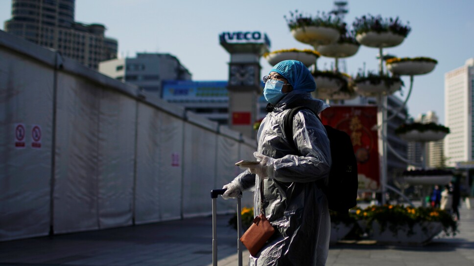 A woman wearing a mask and a plastics rain coat as protection from coronavirus, is seen at a subway station in Shanghai