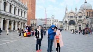 Tourists wear protective masks in Saint Mark's Square in Venice after two coronavirus cases have been confirmed in Italy