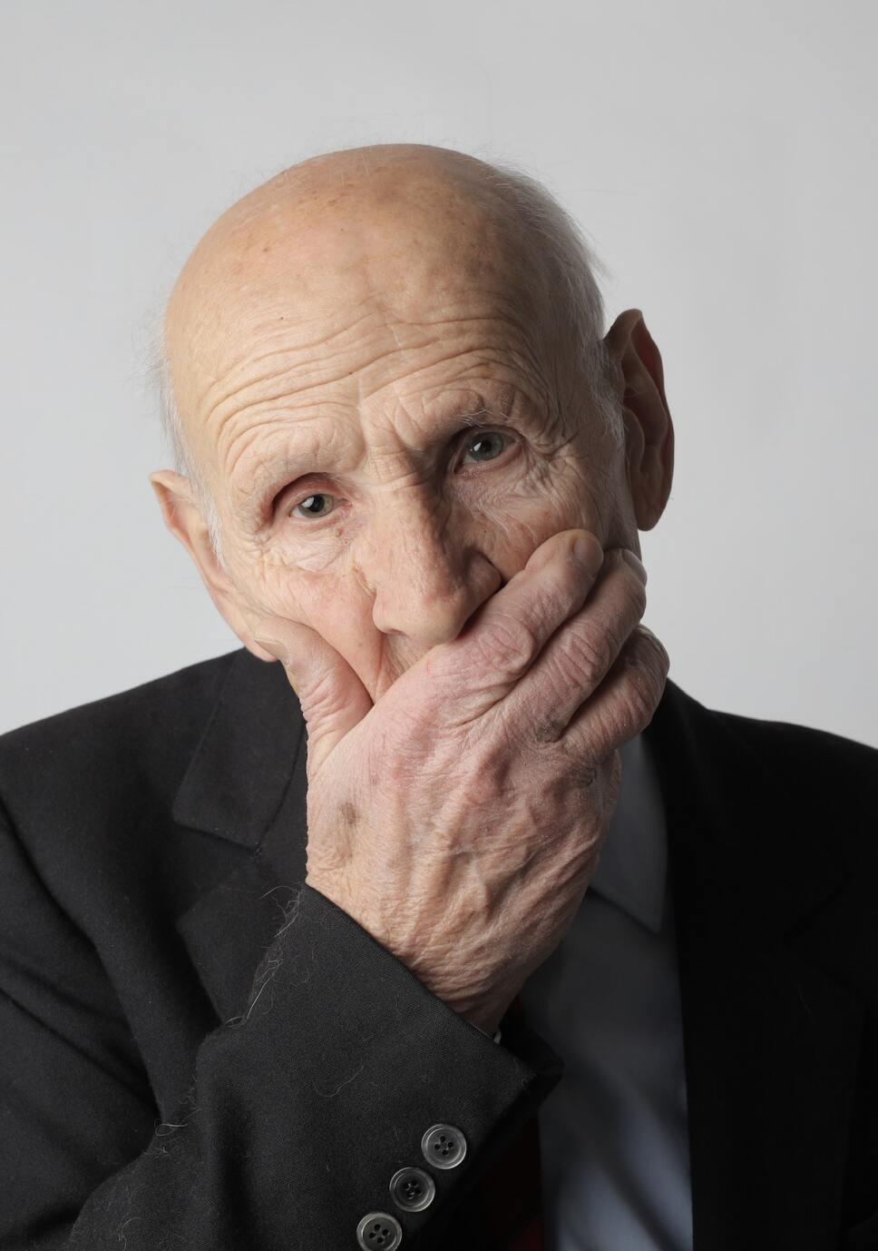 hombre viejo cubriendose el rostro con la mano