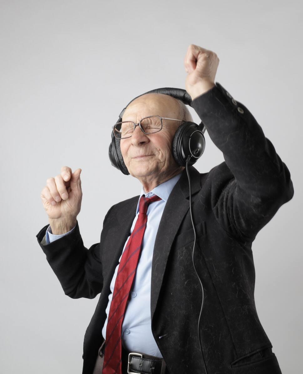 anciano bailando con audifonos y traje