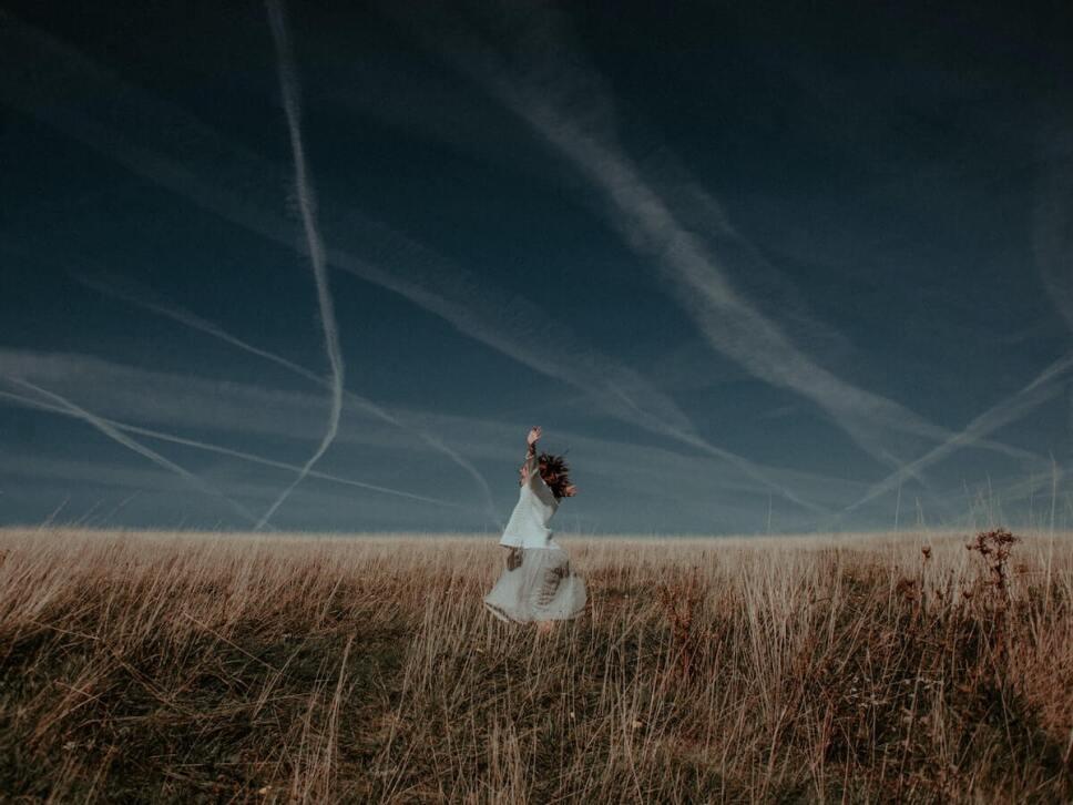 mujer en un campo con los brazos estirados