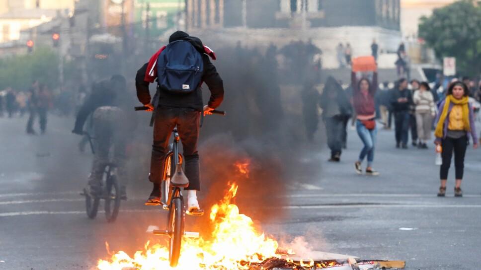 Un manifestante pasa con su bicleta sobre una barricada durante una protesta originada en el alza del transporte