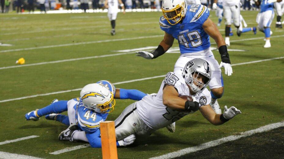 El running back de los Raiders de Oakland Alec Ingold consigue una anotación al superar a los linebackers de los Chargers de Los Ángeles Kyzir White y Drue Tranquill (49) en la primera mitad del juego del jueves 7 de noviembre de 2019, en Oakland,