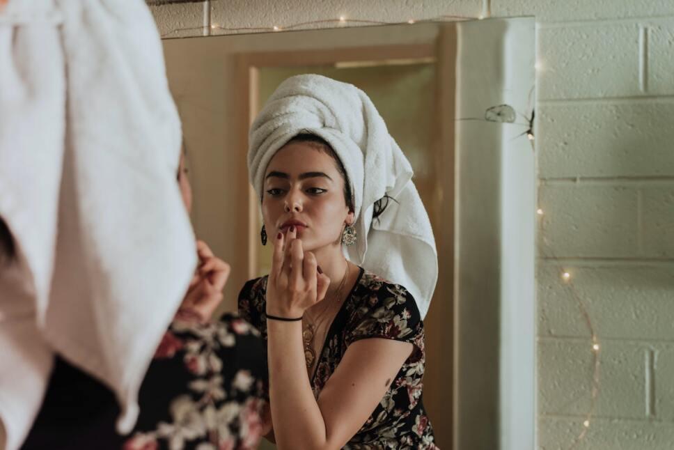 mujer joven arreglandose frente al espejo