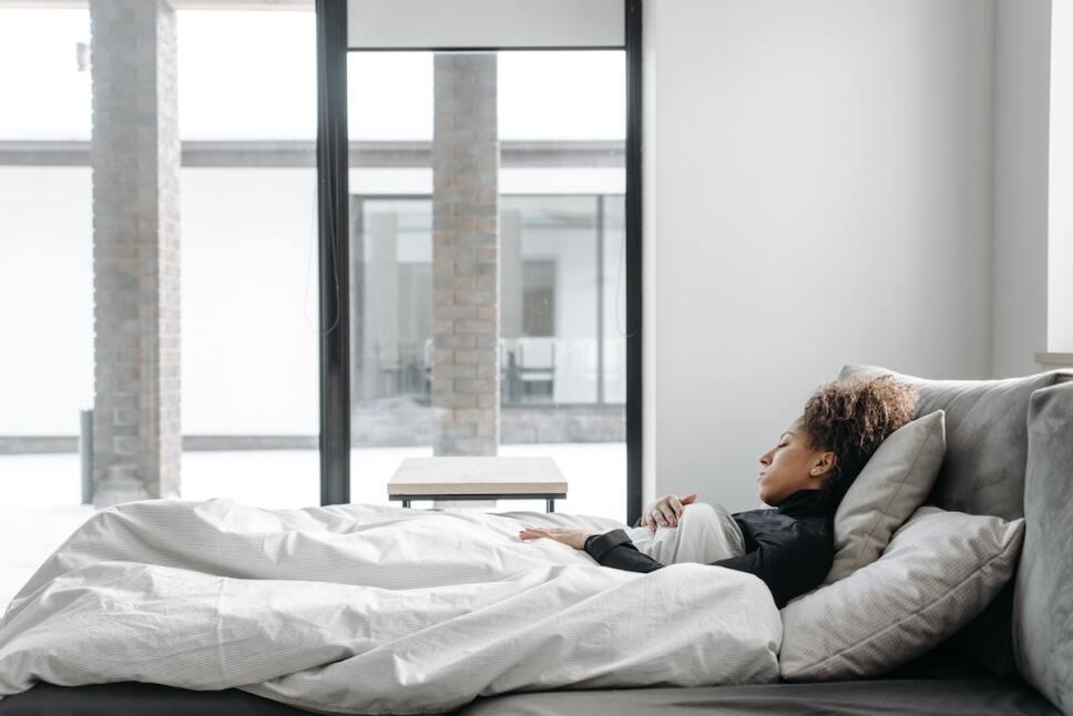 mujer fatigada recostada en cama