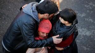 Una familia espera que los trabajadores de rescate encuentren a sus familiares entre las ruinas de un edificio derrumbado tras un terremoto en Elazig