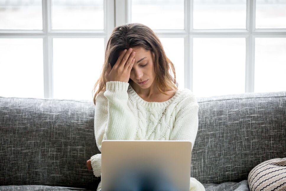 mujer vulnerable sentada en el sillón con su computadora en las piernas