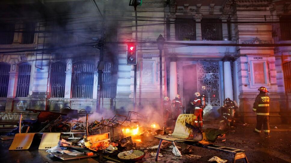 Bomberos intentan sofocar el incendio de muebles y objetos en las afueras del periódico El Mercurio de Valparaíso durante una protesta en contra del gobierno.