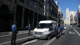 Oficiales de la policía municipal con mascarillas comprueban un coche en la Gran Vía durante el brote de coronavirus (COVID-19) en Madrid