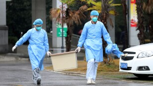 FILE PHOTO: Medical staff carry a box as they walk at the Jinyintan hospital, where the patients with pneumonia caused by the new strain of coronavirus are being treated, in Wuhan