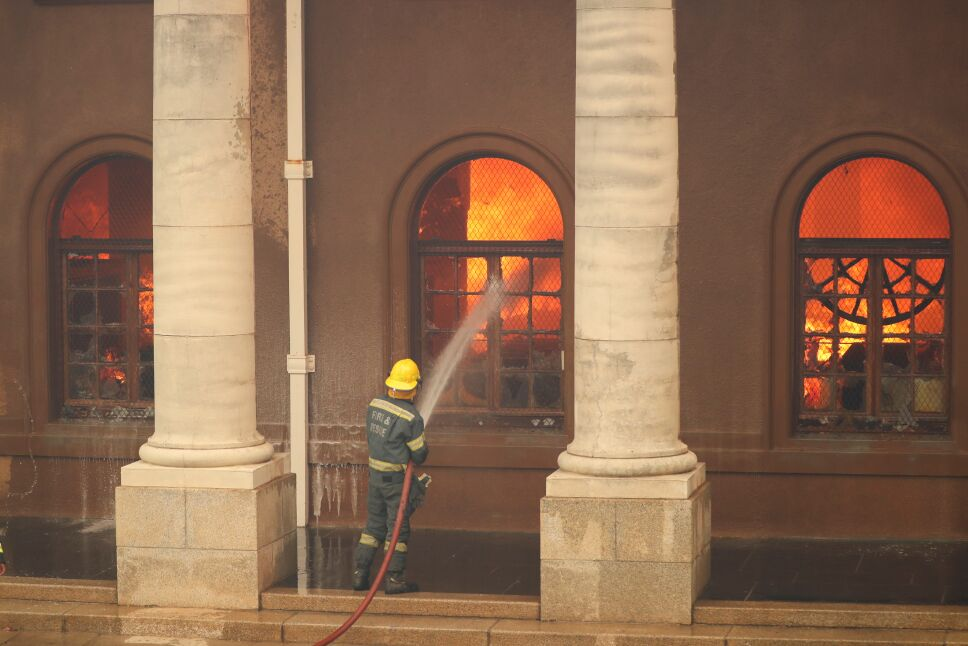 Firefighters battle flames as the library at the University of Cape Town burns, in Cape Town