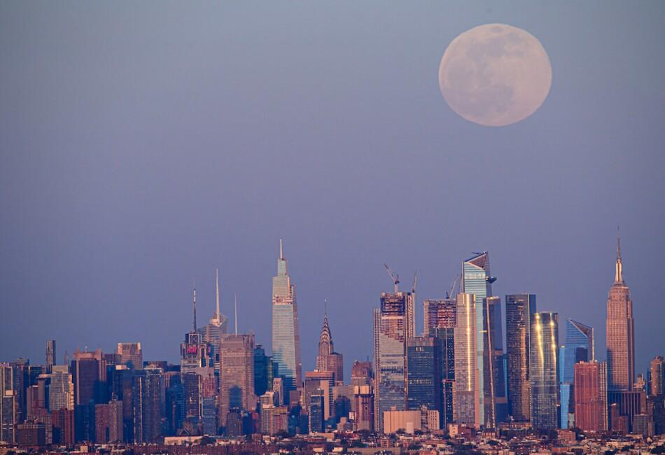 Vista de la Superluna rosa del sobre el skyline más famoso del mundo, Nueva York, en el que su enorme tamaño contrasta con los altos edificios de la ciudad. / Foto: Angela Weiss / AFP