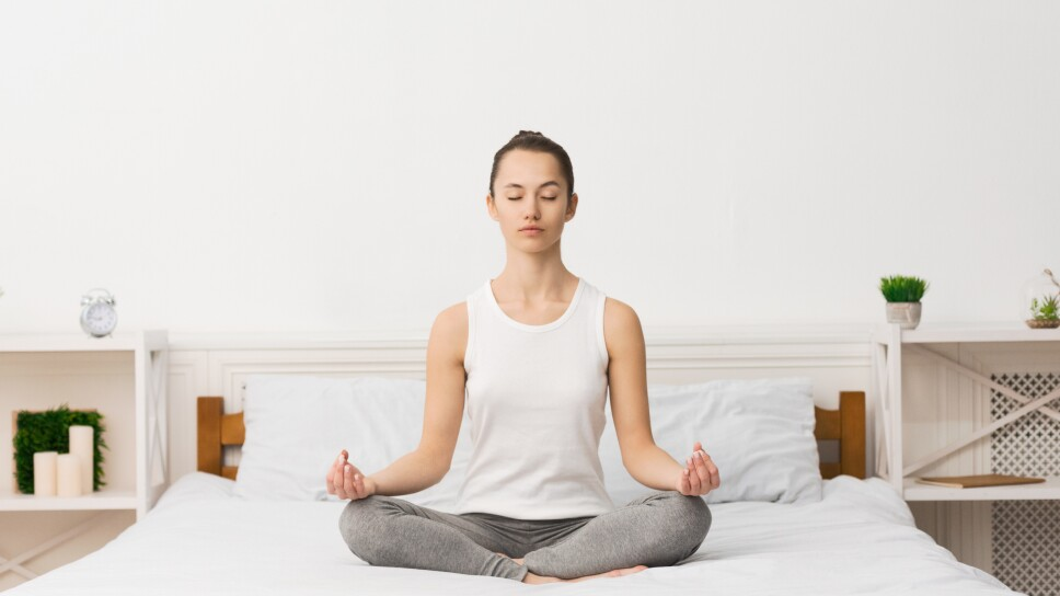 Young sporty woman practicing yoga after waking up
