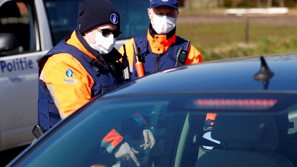 Belgian police officers wearing a protective mask control a driver on the Belgian-Dutch border in Meersel-Dreef