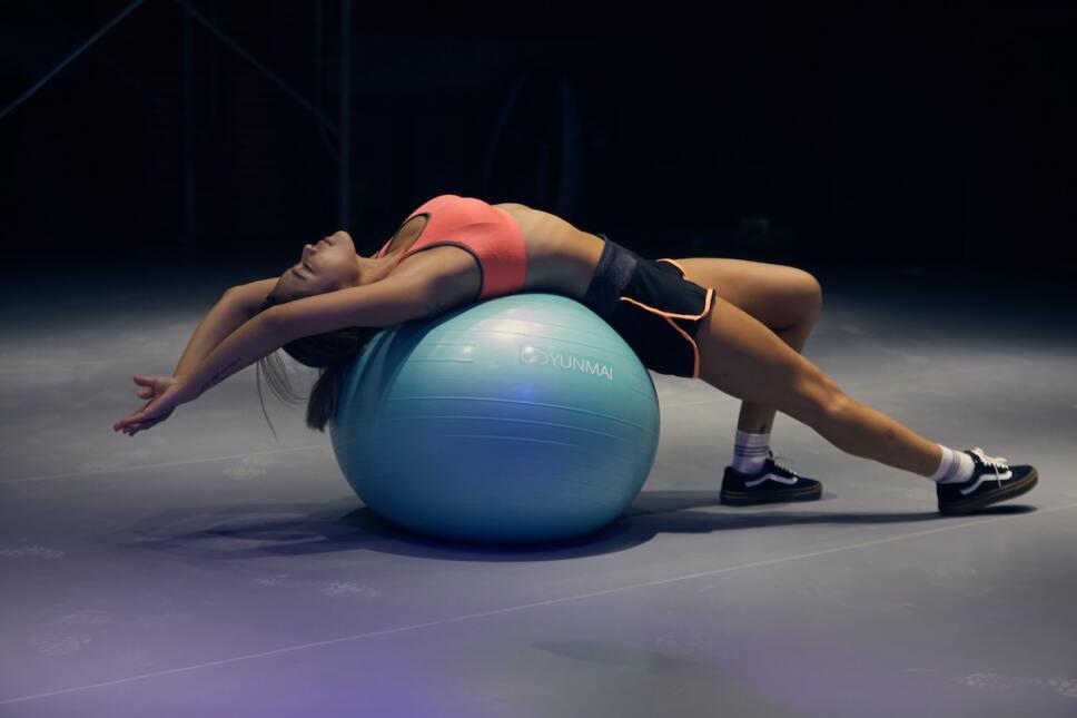 mujer sobre pelota de ejercicio cardio