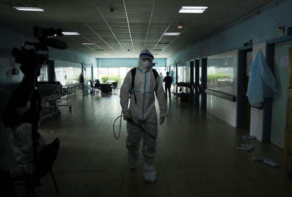 Un trabajador de la salud, vestido con traje protector y mascarilla, camina mientras se prepara para desinfectar un pasillo de un hospital después de que se confirmara un caso de ébola en Abiyán, Costa de Marfil.