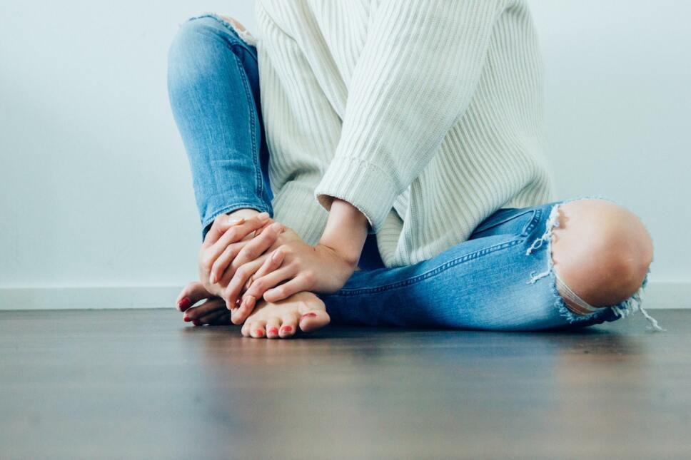 mujer sosteniendo su tobillo con dolor