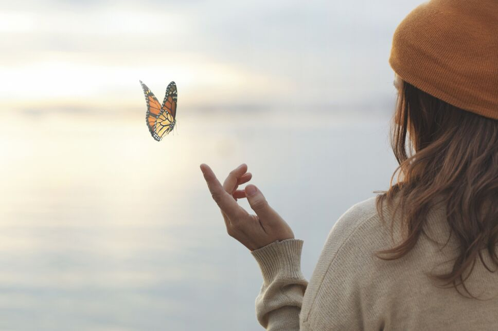 colorful butterfly is laying on a woman's hand