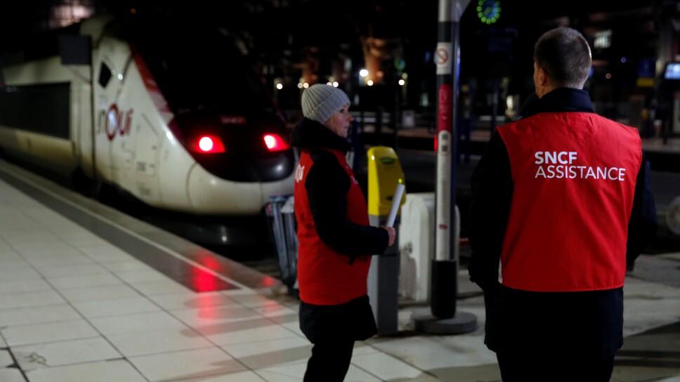 Trabajadores ferroviarios franceses de la SNCF se paran en una plataforma para prestar asistencia a los pasajeros del ferrocarril de Lille durante una jornada de huelga nacional y protestas contra los planes de reforma de las pensiones del gobierno francé
