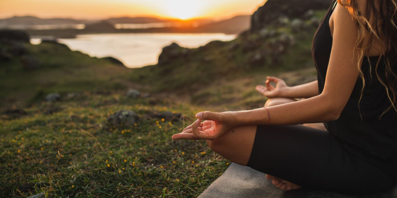 Healthy Lifestyle and Yoga Concdvndfvdept. Close-up hands. Woman do yoga outdoors at sunrise in lotus position. Woman exercising and meditating in morning. Nature background.