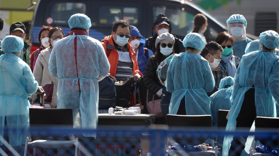 Foto de archivo. Trabajadores ayudan a los pasajeros cuando salen del crucero Diamond Princess, en la Terminal de Cruceros Daikoku Pier, en Yokohama, Japón.