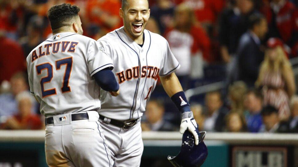 El puertorriqueño Carlos Correa, de los Astros de Houston, festeja con el venezolano José Altuve, tras conectar un jonrón de dos carreras en el quinto juego de la Serie Mundial ante los Nacionales de Washington, el domingo 27 de octubre de 2019. I