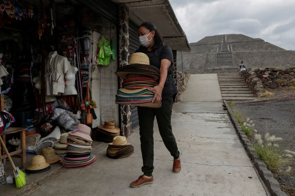 A local vendor carries hats during the start of the gradual reopening of the ancient ruins of Teotihuacan