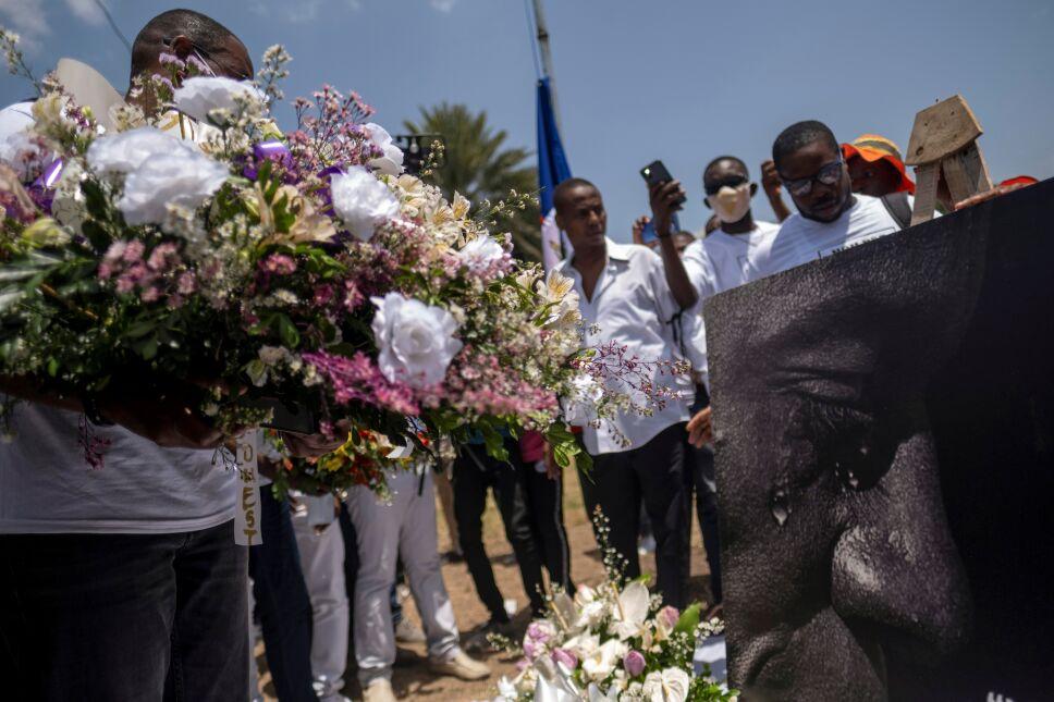 Personas con flores se reúnen en un monumento ubicado frente al Palacio Presidencial en memoria del presidente Jovenel Moïse a una semana después de su asesinato, en Puerto Príncipe, Haití, el 14 de julio de 2021.