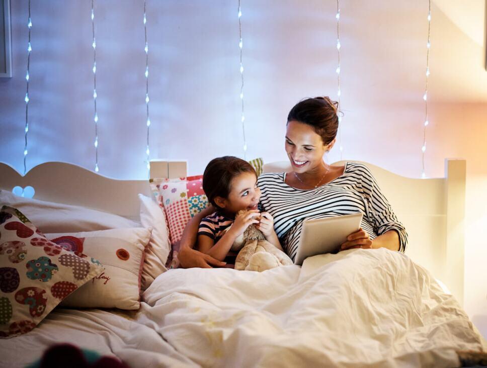 madre leyendole a su hija un cuento en cama
