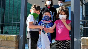 FOTO DE ARCHIVO: Una familia posa para una foto después de recibir pescado recién capturado por voluntarios, mientras Italia permanece encerrada para combatir la propagación de la enfermedad coronavirus (COVID-19), en la ciudad toscana de Castiglione de