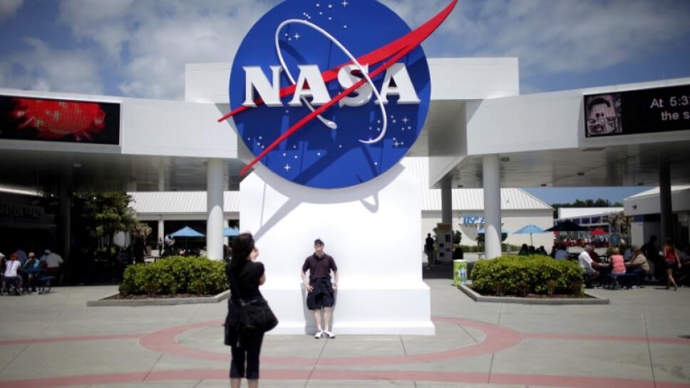 Imagen de archivo de turistas tomando fotografías de un logo de la NASA en el complejo para visitantes del Centro Espacial Kennedy en Cabo Cañaveral, Florida