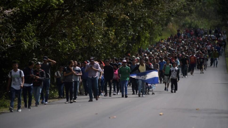 Hondureños, parte de una caravana de migrantes que se dirigen hacia Estados Unidos, caminan por una carretera después de romper un bloqueo realizado por los policías de Guatemala en la frontera entre Honduras y Guatemala, en Esquipulas