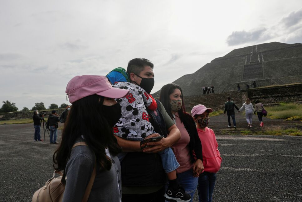 Members of a family look on as they wear protective masks during the start of the gradual reopening of the ancient ruins of Teotihuacan