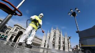 Un trabajador con ropa de protección desinfecta la plaza del Duomo, durante el brote de coronavirus (COVID-19) en el centro de Milán