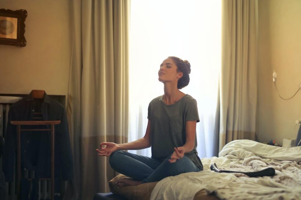 mujer joven meditando en su cama