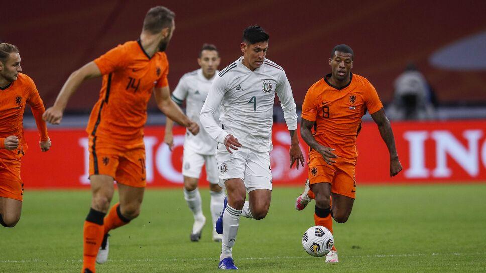 Edson Álvarez de México entre dos jugadores de Holanda
