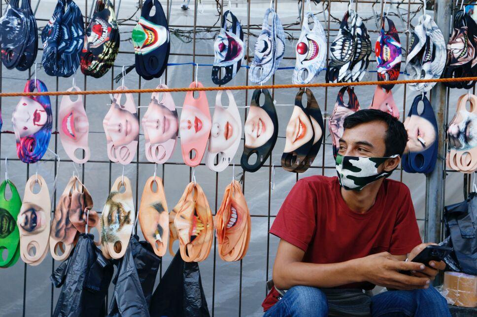 Un vendedor se sienta cerca de una pantalla de máscaras de diseño facial en un mercado tradicional, en medio del brote de la enfermedad por coronavirus (COVID-19), en Yakarta