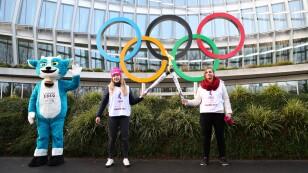 La portadora de la antorcha de los Juegos Olímpicos de la Juventud de Invierno Lausana 2020 Boivin pasa la llama a Locher en el COI en Lausana