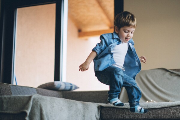 Little boy jumping with joy on sofa