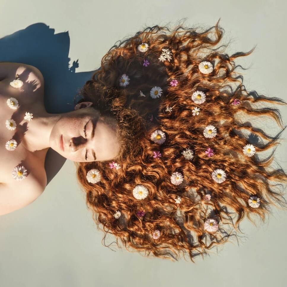 metodo curly hair mujer con flores en el pelo